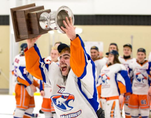 HS hockey player holding trophy overhead